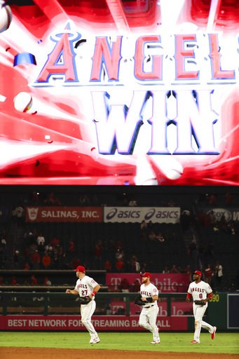 (AP Photo/Chris Carlson). Los Angeles Angels center fielder Mike Trout, from left, right fielder Kole Calhoun and left fielder Justin Upton run off the field after their win against the Texas Rangers during a baseball game in Anaheim, Calif., Tuesday, ...