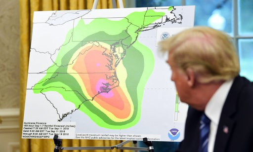 (AP Photo/Susan Walsh). President Donald Trump looks at a chart showing potential rainfall totals from Hurricane Florence during a briefing in the Oval Office of the White House in Washington, Tuesday, Sept. 11, 2018.