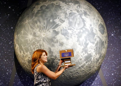 (AP Photo/Rick Bowmer). In this Thursday, Aug. 23, 2018, photo, Lindsie Smith, from the Clark Planetarium, holds moon rocks encased in acrylic and mounted on a wooden plaque at the Clark Planetarium, in Salt Lake City. A former NASA investigator who ha...