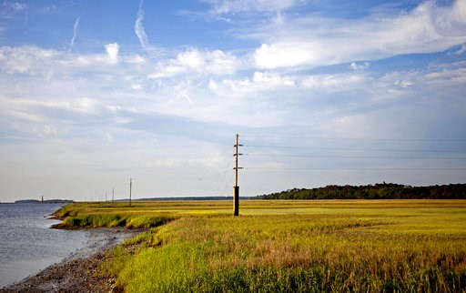 (AP Photo/David Goldman, File). FILE - In this May 16, 2013, file photo, a utility pole stands in the middle of a marsh at sunset on Sapelo Island, Ga., a Gullah-Geechee community. A tight-knit community of slave descendants on the South Carolina coast...