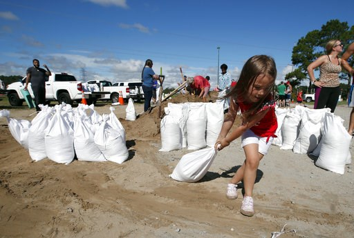 (AP Photo/Alex Brandon). Chloe Heeden, 4, from Virginia Beach, Va., drags a sandbag to her father's car, Wednesday, Sept. 12, 2018, in Virginia Beach, Va., as Hurricane Florence moves towards the eastern shore. The National Hurricane Center's projected...