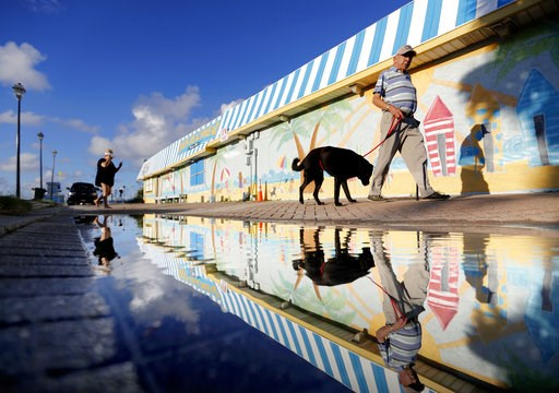 (AP Photo/David Goldman). Beachgoers walk past a mural along the boardwalk as Hurricane Florence approaches the east coast in Atlantic Beach, N.C., Wednesday, Sept. 12, 2018.