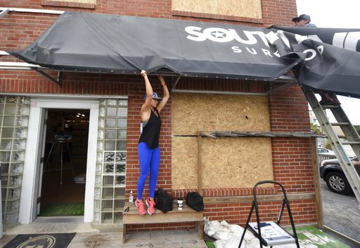 (Matt Born/The Star-News via AP, File). FILE- In this Sept. 11, 2018, file photo Ashley DeGroote, left, and husband Jeff DeGroote remove the awning at South End Surf Shop in Wrightsville Beach, N.C., in preparation for Hurricane Florence. Though it's f...
