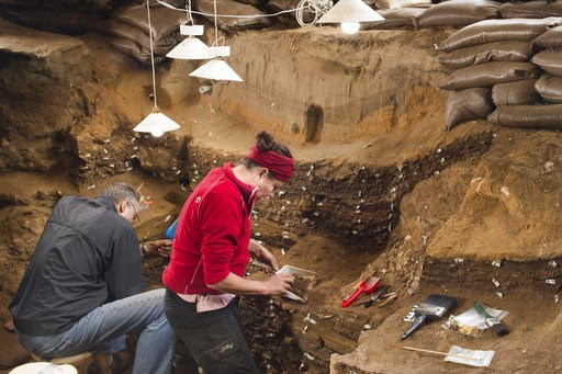 (Magnus M. Haaland via AP). This undated photo provided by Magnus M. Haaland in September 2018 shows researchers in the interior of the Blombos Cave east of Cape Town, South Africa. In a report released on Wednesday, Sept. 12, 2018, scientists say a ti...