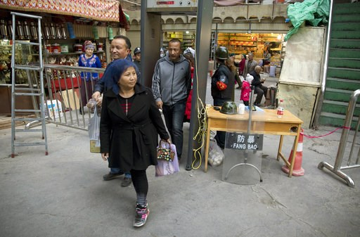 (AP Photo/Ng Han Guan, File). FILE - In this Nov. 4, 2017 photo, residents past through one of the many security check points in Kashgar in western China's Xinjiang region. Two U.S. lawmakers are urging the extension of American export restrictions to ...
