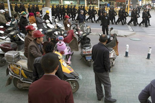 (AP Photo/Ng Han Guan, File). FILE - In this Nov. 5, 2017 file photo, residents watch a convoy of security personnel in a show of force through central Kashgar in western China's Xinjiang region. Two U.S. lawmakers are urging the extension of American ...