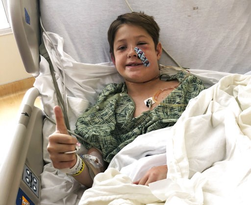 (Shannon Miller via AP). In this Monday, Sept. 10, 2018 photo provided by Shannon Miller, his son Xavier Cunningham, of Harrisonville, Mo., gives a thumbs up while recovering at the University of Kansas Hospital in Kansas City, Kan., after surgery to r...