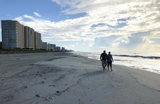 (AP Photo/Jeffery Collins). Chris and Nicole Roland walk down a beach in North Myrtle Beach, S.C. on Wednesday, Sept. 12, 2018. The couple boarded up their uncle's condominium and are leaving soon as Hurricane Florence approaches.
