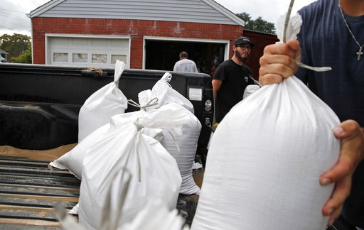 (AP Photo/Alex Brandon). Seth Bazemore IV, center moves sandbags, Tuesday, Sept. 11, 2018, in the Willoughby Spit area of Norfolk, Va., as they make preparations for Hurricane Florence.