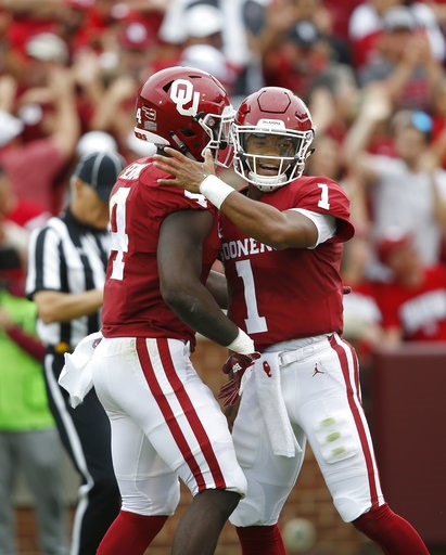(AP Photo/Sue Ogrocki, File). FILE - In this Saturday, Sept. 8, 2018, file photo, Oklahoma quarterback Kyler Murray (1) celebrates a touchdown with teammate Trey Sermon (4) in the first half of an NCAA college football game against UCLA in Norman, Okla...