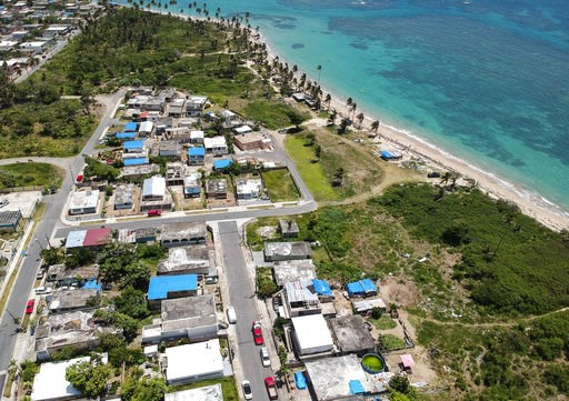 (AP Photo/Dennis M. Rivera, File). FILE - This June 18, 2018 file photo shows an aerial photo of the Viequez neighborhood, east of San Juan, Puerto Rico, where people were still living in damaged homes, protected by blue plastic tarps, nine months sinc...