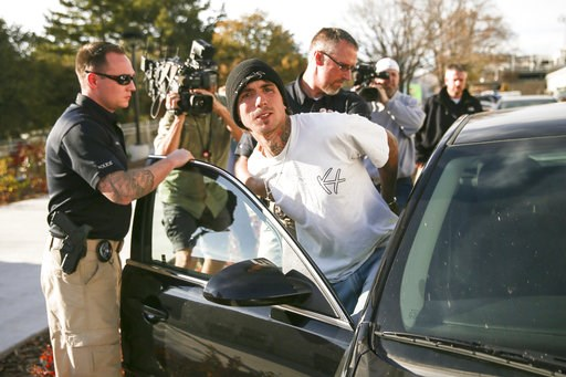 (Spenser Heaps/The Deseret News via AP, file). FILE - In this Oct. 31, 2017, file photo, Austin Boutain, a suspect in the fatal shooting of University of Utah student Chenwei Guo, is led out of the University of Utah Department of Public Safety in Salt...