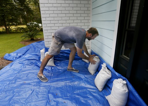 (Grace Beahm Alford/The Post And Courier via AP). Stewart Thomason places sandbags that he used for previous hurricanes and tarp to prevent the flooding from rain at his home on the Isle of Palms,S.C. ahead of Hurricane Florence on Wednesday, Sept. 12,...