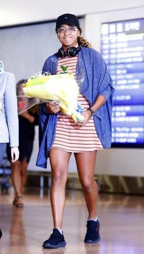(Yohei Fukai/Kyodo News via AP). Japan's Naomi Osaka arrives at Haneda airport in Tokyo. Osaka defeated Serena Williams of the U.S. on Saturday, Sept. 8, to become the first Grand Slam singles champion from Japan.