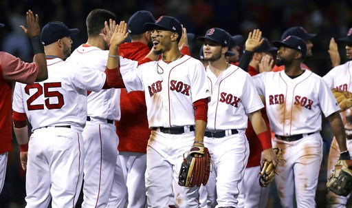 (AP Photo/Charles Krupa). Boston Red Sox right fielder Mookie Betts, center, celebrates with teammates after defeating the Toronto Blue Jays 1-0 for the team's 100th win of the season after a baseball game at Fenway Park in Boston, Wednesday, Sept. 12,...