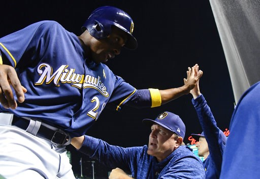 (AP Photo/Matt Marton). Milwaukee Brewers' Curtis Granderson (28) celebrates with bench coach Pat Murphy, center, and manager Craig Counsell, right, after he scores during the third inning of a baseball game against the Chicago Cubs on Wednesday, Sept....