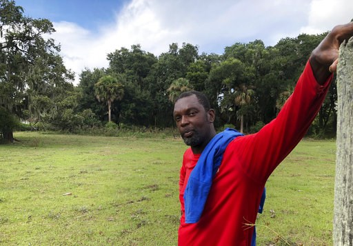 (AP Photo/Russ Bynum). In this Sept. 11, 2018 photo, John Brown stands behind a fence for his cows outside his home on St. Helena Island, S.C. Brown and other residents of the island's Gullah community of slave descendants are watching Hurricane Floren...