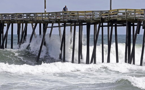 (AP Photo/Gerry Broome). Waves crash under a pier in Kill Devil Hills, N.C., Wednesday, Sept. 12, 2018, as Hurricane Florence approaches the east coast.