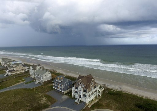 (AP Photo/Tom Copeland). A storm front passes homes in North Topsail Beach, N.C., prior to Hurricane Florence moving toward the east coast on Wednesday, Sept. 12, 2018.