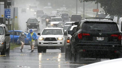 (Matthew Thayer/The News via AP). A couple walks in a rainstorm amid heavy traffic in Paia, Hawaii, on Tuesday, Sept. 11, 2018, as Tropical Storm Olivia marched closer to Maui. Olivia was expected to pass directly over Maui on Tuesday night into Wednes...