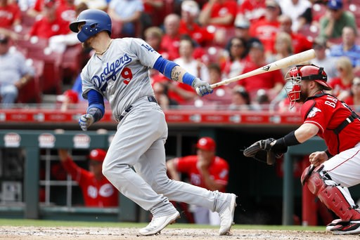 (AP Photo/John Minchillo). Los Angeles Dodgers' Yasmani Grandal hits an RBI single off Cincinnati Reds relief pitcher Wandy Peralta in the fifth inning of a baseball game, Wednesday, Sept. 12, 2018, in Cincinnati.