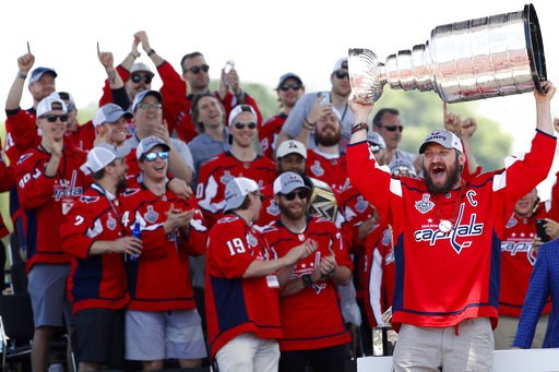 (AP Photo/Jacquelyn Martin, File). FILE - In this June 12, 2018, file photo, Washington Capitals' Alex Ovechkin, from Russia, right, holds up the Stanley Cup during a victory rally in Washington. The celebrating is over for now for the Capitals after p...