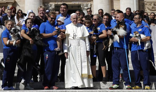 (AP Photo/Alessandra Tarantino). Pope Francis poses with members of an association of dogs' trainers at the end of his general audience in St. Peter's Square at the Vatican Wednesday, Sept. 12, 2018.