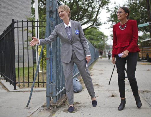 (AP Photo/Seth Wenig). New York democratic gubernatorial candidate Cynthia Nixon, left, and congressional candidate Alexandria Ocasio-Cortez greet voters and children outside of a school while campaigning in New York, Wednesday, Sept. 12, 2018. Democra...