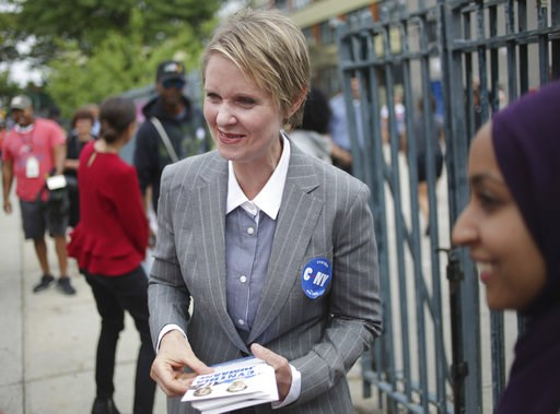 (AP Photo/Seth Wenig). New York democratic gubernatorial candidate Cynthia Nixon talks with a voter while campaigning outside of a school in New York, Wednesday, Sept. 12, 2018. Democratic primary voters in New York on Thursday, will soon settle the co...