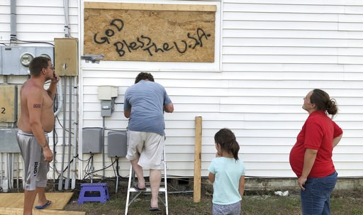 (AP Photo/Jeffrey Collins). In this Wednesday, Sept. 12, 2018, photo Mercedes O'Neill, right, her 6-year-old daughter Sophie, her boyfriend Kelly Johnson, left and neighbor Shawn Dalton on ladder put plywood on the window of their home in North Myrtle ...