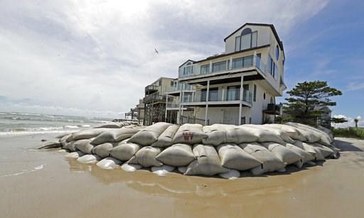 (AP Photo/Chuck Burton, File). Sand bags surround homes on North Topsail Beach, N.C., Wednesday, Sept. 12, 2018, as Hurricane Florence threatens the coast.