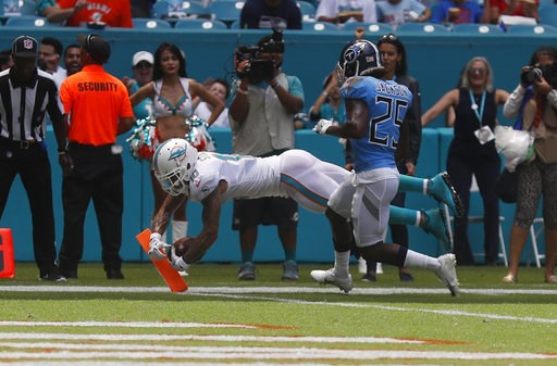 (AP Photo/Brynn Anderson). Miami Dolphins wide receiver Kenny Stills (10) scores a touchdown ahead of Tennessee Titans cornerback Adoree' Jackson (25), during the first half of an NFL football game, Sunday, Sept. 9, 2018, in Miami Gardens, Fla.