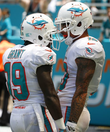 (AP Photo/Wilfredo Lee). Miami Dolphins wide receiver Jakeem Grant (19) celebrates with wide receiver Kenny Stills (10) after Stills scored a touchdown, during the first half of an NFL football game against the Tennessee Titans, Sunday, Sept. 9, 2018, ...