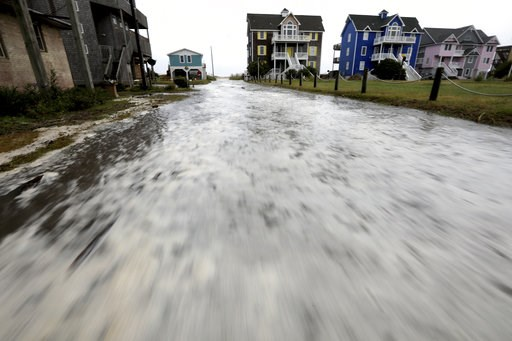 (Steve Earley /The Virginian-Pilot via AP). Ocean water rushes down Cape Hatteras Pier Drive in Frisco, N.C.,  on Hatteras Island as the effects of Hurricane Florence reach the area on Thursday, Sept. 13, 2018.