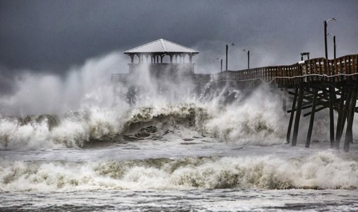 (Travis Long/The News & Observer via AP). Waves slam the Oceana Pier & Pier House Restaurant in Atlantic Beach, N.C.,  Thursday, Sept. 13, 2018 as Hurricane Florence approaches the area.