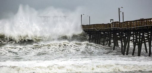 (Travis Long /The News & Observer via AP). Waves slam the Oceana Pier & Pier House Restaurant in Atlantic Beach, N.C.,  Thursday, Sept. 13, 2018 as Hurricane Florence approaches the area.