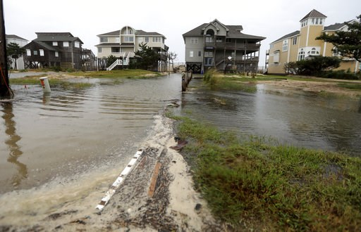 (Steve Earley/The Virginian-Pilot via AP). Ocean water breeches to the dunes in Avon, N.C., as the first effects of Hurricane Florence reach Hatteras Island on Thursday, Sept. 13, 2018.