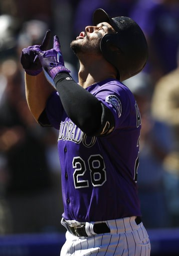 (AP Photo/David Zalubowski). Colorado Rockies' Nolan Arenado gestures as he crosses home plate after hitting a solo home run off Arizona Diamondbacks starting pitcher Matt Koch in the first inning of a baseball game Thursday, Sept. 13, 2018, in Denver.