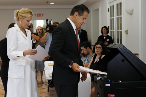 (AP Photo/Richard Drew). New York Gov. Andrew Cuomo, accompanied by his girlfriend Sandra Lee, puts his primary election ballot in a scanner at the Presbyterian Church of Mount Kisco, in Mt. Kisco, NY, Thursday, Sept. 13, 2018.