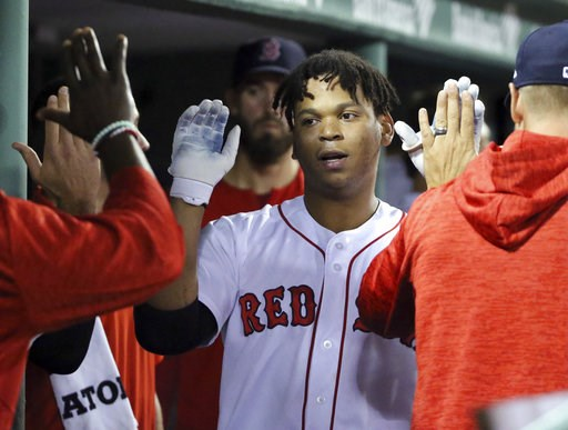 (AP Photo/Elise Amendola). Boston Red Sox's Rafael Devers celebrates his solo home run in the dugout in the sixth inning of a baseball game against the Toronto Blue Jays at Fenway Park, Thursday, Sept. 13, 2018, in Boston.