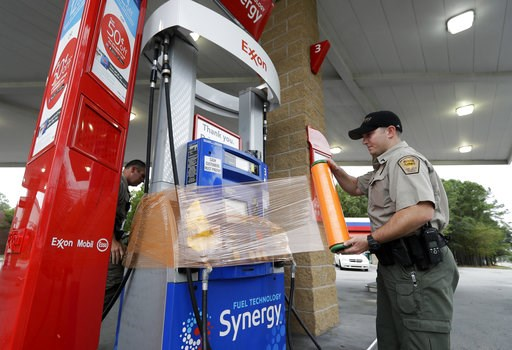 (AP Photo/Chuck Burton). New Hanover Sheriff's Corp. N. Brothers wraps a gas pump for protection in Wilmington, N.C., as Hurricane Florence threatens the coast Thursday, Sept. 13, 2018.