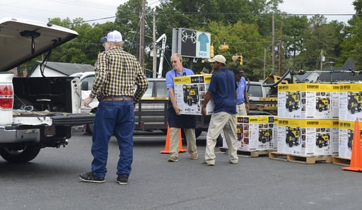 (Janet S. Carter/Daily Free Press via AP). Allen Cahoon and Toby Bryant load a generators for a customer Thursday, Sept. 13, 2018 at Big Blue Store in Kinston NC..