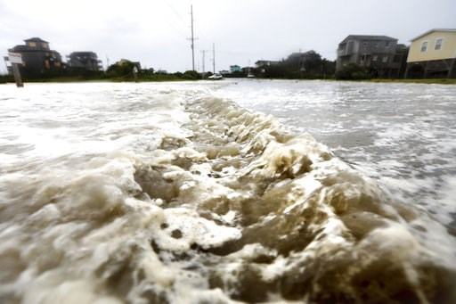 (Steve Earley /The Virginian-Pilot via AP). Ocean waters rushes down Hwy 12 in Frisco, N.C., on Hatteras Island as the effects of Hurricane Florence breach the dune line on Thursday, Sept. 13, 2018.