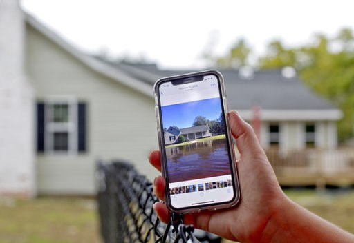 "(AP Photo/David Goldman). Jodi Pajaro shows an image of the water which surrounded her home from Hurricane Matthew two years ago in Nichols, S.C., Thursday, Sept. 13, 2018. ""Florence has us on pins and needles,"" said Pajaro whose nearly 100-year-old ho..."