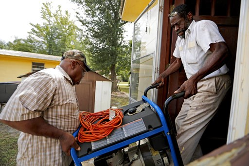 (AP Photo/David Goldman). Thomas Lee, left, gets help from Stoney Williamson, right, lifting a generator into his home which flooded two years ago from Hurricane Matthew in Nichols, S.C., Thursday, Sept. 13, 2018. Few places in South Carolina are more ...