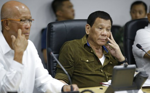 (AP Photo/Aaron Favila). Philippine President Rodrigo Duterte, center,  and Philippine Defense Secretary Delfin Lorenzana, left, attend a command conference on Typhoon Mangkhut, locally named Typhoon Ompong, at the National Disaster Risk Reduction and ...