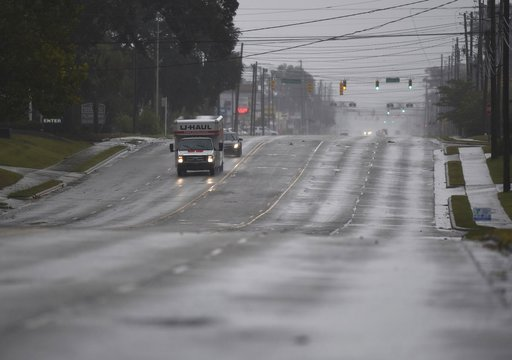 (Matt Born/The Star-News via AP). A few cars drive along an almost deserted Market St. in Wilmington, N.C., Thursday, Sept. 13, 2018. Florence's outer bands of wind and rain began lashing North Carolina on Thursday.