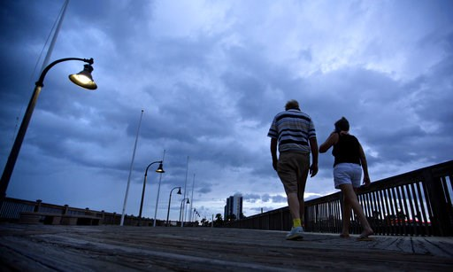 (AP Photo/David Goldman). A couple walks along the boardwalk as Hurricane Florence approaches Myrtle Beach, S.C., Thursday, Sept. 13, 2018.
