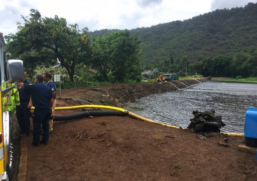 (AP Photo/Caleb Jones). Officials pump water from a reservoir where a dam came close to overflowing in Honolulu on Thursday, Sept. 13, 2018. Honolulu officials say they may need to evacuate 10,000 people from a residential neighborhood if water in the ...