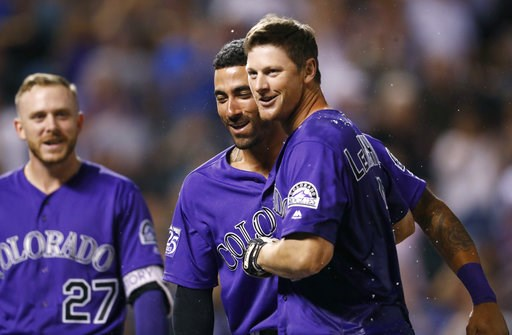 (AP Photo/David Zalubowski). Colorado Rockies' DJ LeMahieu, right, is congratulated after hitting a two-run home run by Ian Desmond, center, and Trevor Story to defeat the Arizona Diamondbacks in the ninth inning of a baseball game, Wednesday, Sept. 12...